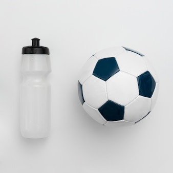 Bovenaanzicht van fles water met voetbal