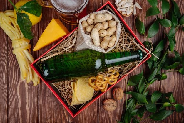 Bovenaanzicht van flesje bier met pinda's in een zak chips en mini pretzels op stro in een rode doos en een mok bier met kaas en citroen op rustiek
