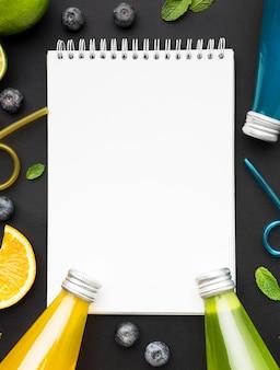 Bovenaanzicht van flessen met frisdrank en notitieboekje