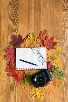Bovenaanzicht van fotocamera, beurt met pen en bril omgeven door rood
