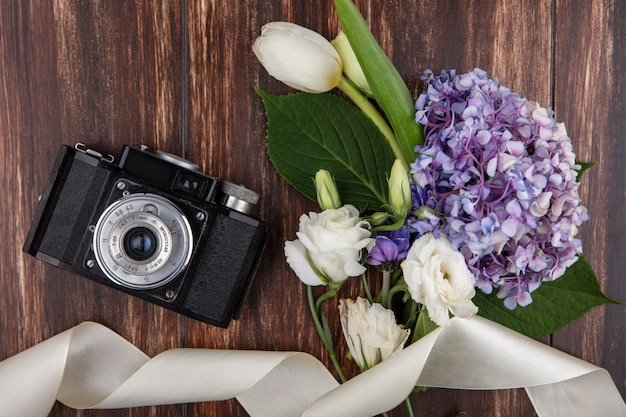 Bovenaanzicht van fotocamera en bloemen met wit lint op houten achtergrond