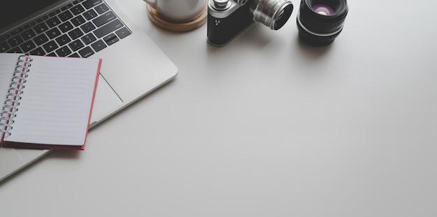 Bovenaanzicht van fotograaf werkplek met laptop, camera's en kantoorbenodigdheden