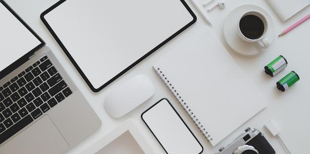 Bovenaanzicht van fotograaf werkplek met leeg scherm tablet, laptop, vintage camera en kantoorbenodigdheden