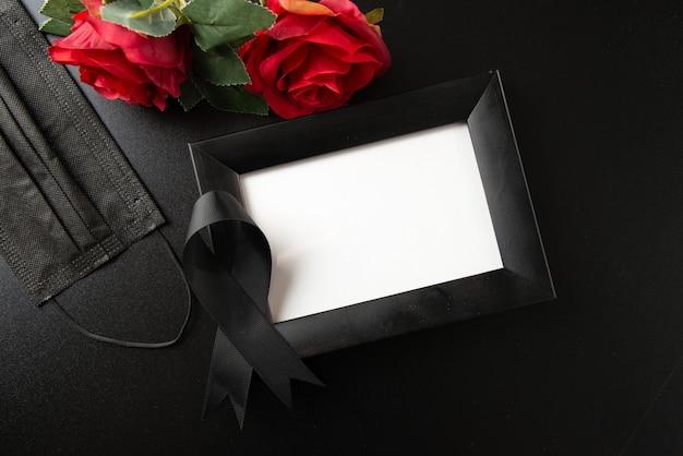 Bovenaanzicht van fotolijst met zwarte strik op donkere muur