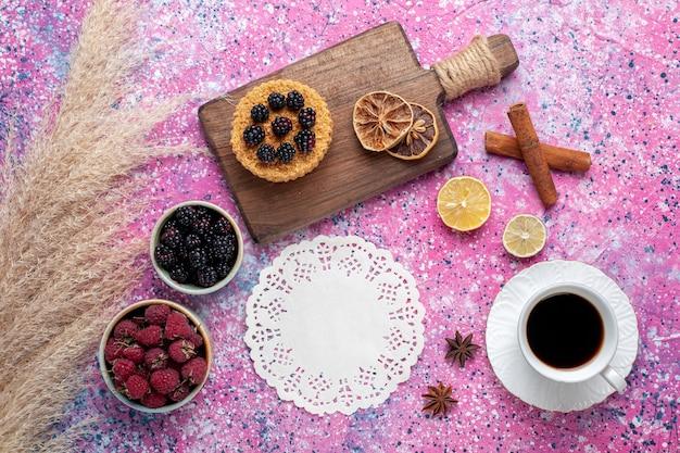Bovenaanzicht van frambozen en bramen in kleine potjes met kopje thee kaneel op lichtroze oppervlak
