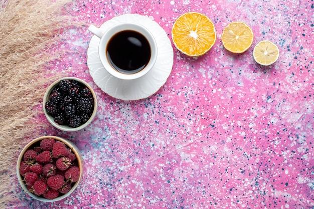 Bovenaanzicht van frambozen en bramen in kleine potten met kopje thee op lichtroze oppervlak