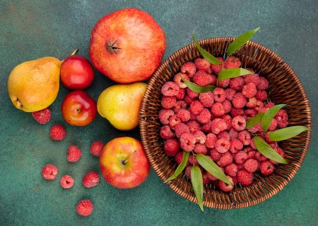 Bovenaanzicht van frambozen in kom en patroon van granaatappel perzik appel pruim op groene ondergrond