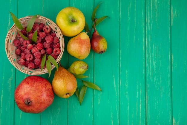 Bovenaanzicht van frambozen in mand met granaatappel perzik en appel op groene ondergrond