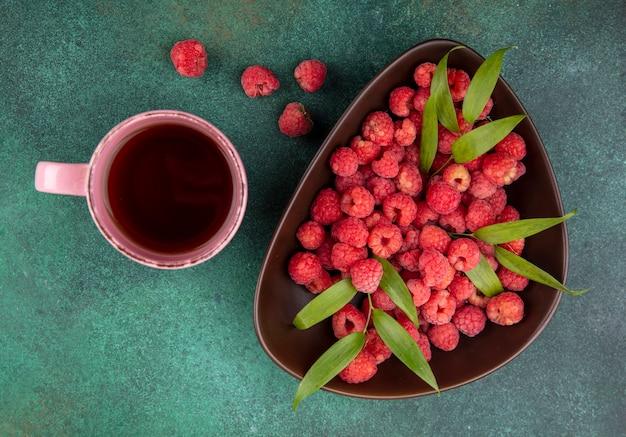 Bovenaanzicht van frambozen met bladeren in kom en kopje thee met frambozen op groene ondergrond