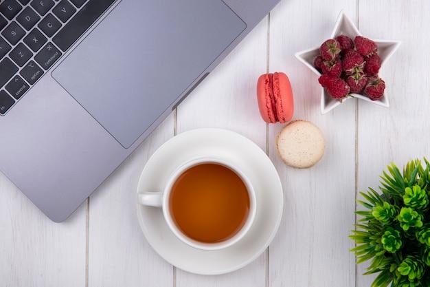 Bovenaanzicht van frambozen met een kopje thee bitterkoekjes en een laptop op een wit oppervlak