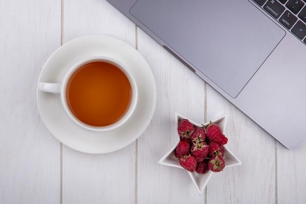 Bovenaanzicht van frambozen met een kopje thee en een laptop op een wit oppervlak