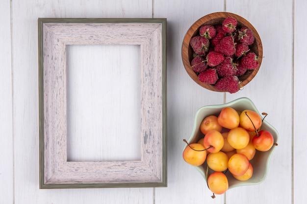 Bovenaanzicht van frambozen met wit frame en witte kers op een wit oppervlak