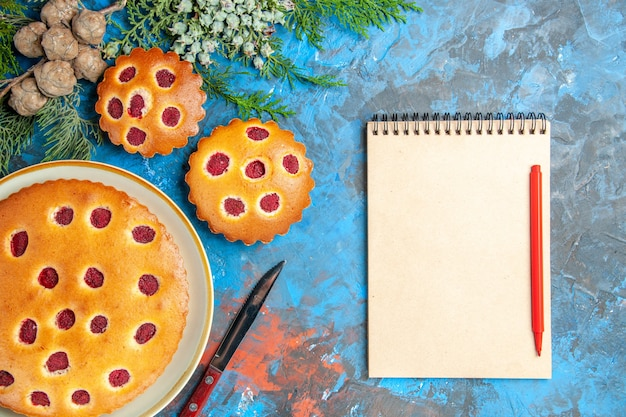 Bovenaanzicht van frambozencake met notitieboekje op blauwe ondergrond