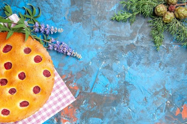 Bovenaanzicht van frambozencake op de vertakking van de de pijnboomboom van de keukendoek op blauwe oppervlakte