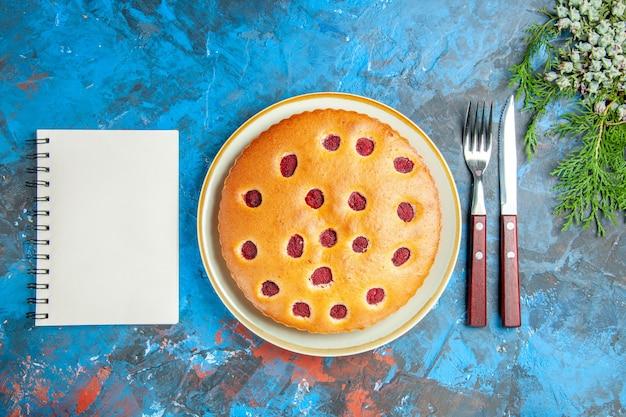 Bovenaanzicht van frambozencake op ovale plaat kegels vork mes een notitieboekje op blauwe ondergrond