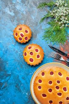 Bovenaanzicht van frambozencake op plaat met mes en vork op blauwe ondergrond