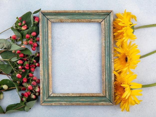 Bovenaanzicht van frame met bloemen aan zijkanten op wit met kopie ruimte