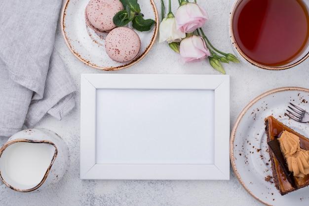 Bovenaanzicht van frame met cake en macarons