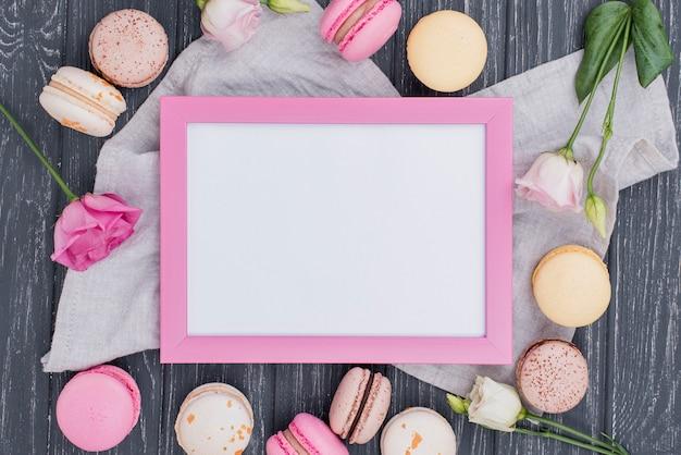 Bovenaanzicht van frame met macarons en rozen
