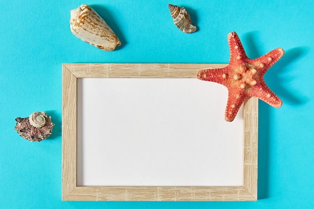 Bovenaanzicht van frame met schelpen en zeester op blauw. zomervakantie concept. zee plat lag