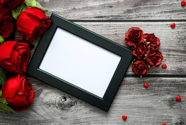 Bovenaanzicht van frame, rode rozen en hart op houten met copyspace voor valentijn, liefde en bruiloft concept.