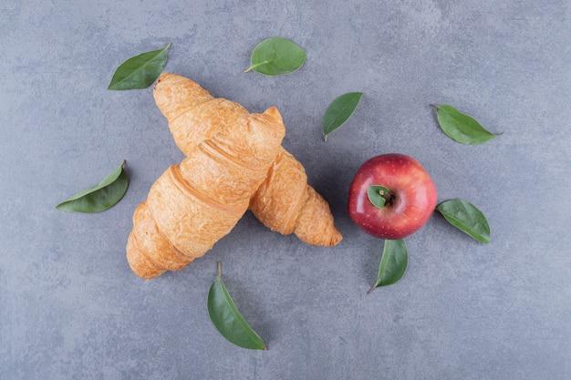 Bovenaanzicht van franse croissants en verse appel op grijze achtergrond.