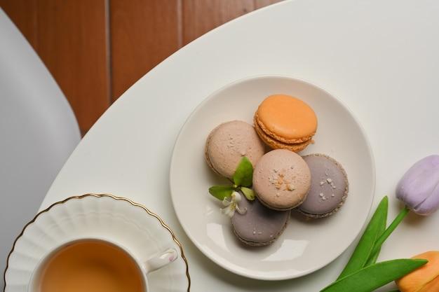 Bovenaanzicht van franse kleurrijke macarons, kopje thee en tulpen bloeien op salontafel in de woonkamer