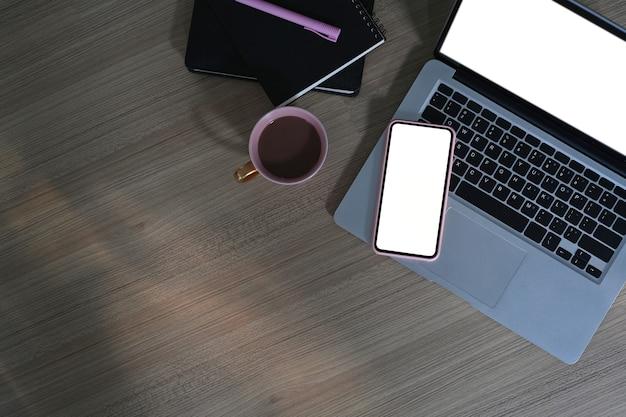 Bovenaanzicht van freelancer werkruimte met leeg scherm laptop, mobiele telefoon, koffiekopje en notebook op houten tafel.