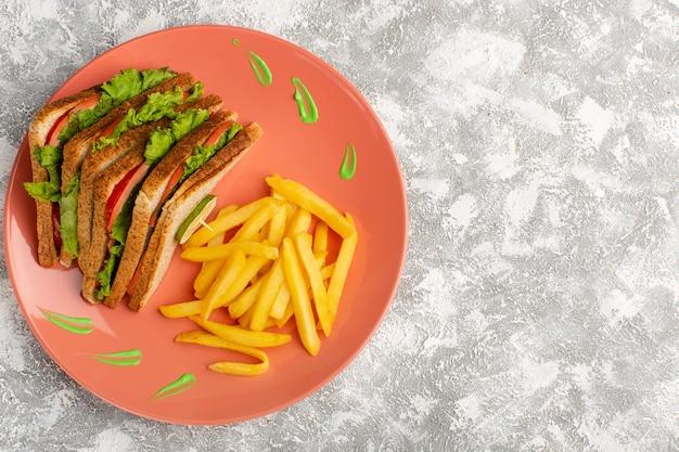 Bovenaanzicht van frietjes en sandwiches in perzik plaat op het grijze lichte oppervlak