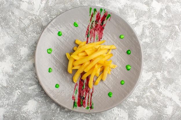 Bovenaanzicht van frietjes gekookt en gezouten binnen plaat op het grijze lichte oppervlak