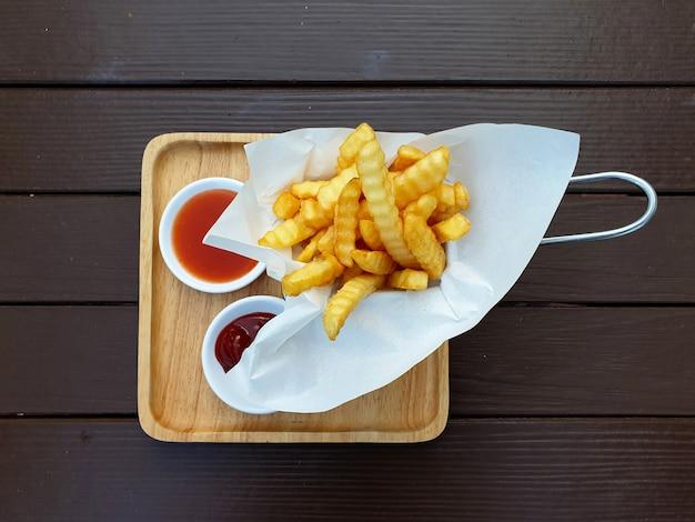 Bovenaanzicht van frietjes in de mand met chili en tomatensaus op een houten tafel achtergrond