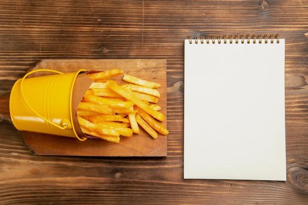 Bovenaanzicht van frietjes in kleine mand met notitieblok op bruine tafel brown