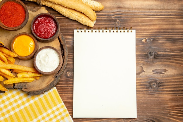 Bovenaanzicht van frietjes met brood en kruiden op bruin houten tafel fastfood maaltijd aardappel peper pittig