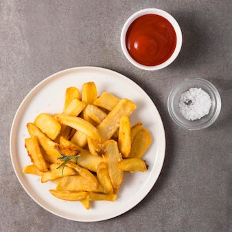 Bovenaanzicht van frietjes met ketchup en zout