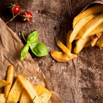 Bovenaanzicht van frietjes met kruiden en tomaten