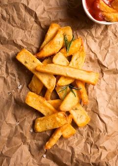 Bovenaanzicht van frietjes op papier met kruiden en ketchup
