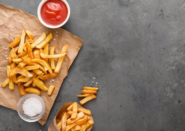 Bovenaanzicht van frietjes op papier met zout en kopie ruimte