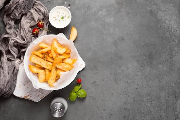 Bovenaanzicht van frietjes op plaat met zoutvaatje en kopie ruimte