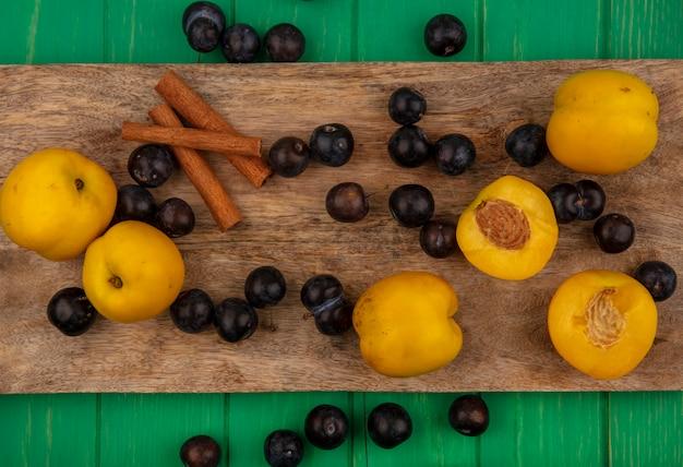 Bovenaanzicht van fruit als abrikozen en sleedoornbessen met kaneel op snijplank op groene achtergrond