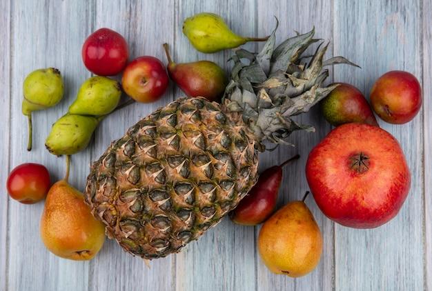 Bovenaanzicht van fruit als ananas perzik pruim granaatappel op houten oppervlak