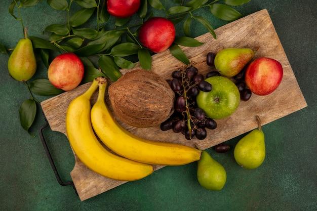 Bovenaanzicht van fruit als druif perzik peer appel banaan kokosnoot op snijplank met bladeren op groene achtergrond