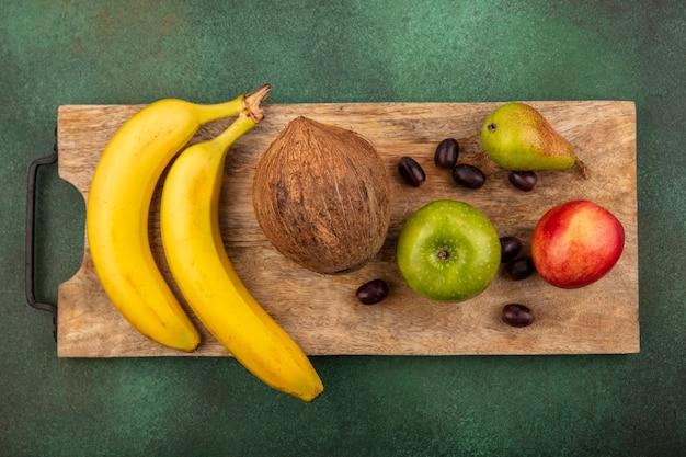 Bovenaanzicht van fruit als druif perzik peer appel banaan kokosnoot op snijplank op groene achtergrond
