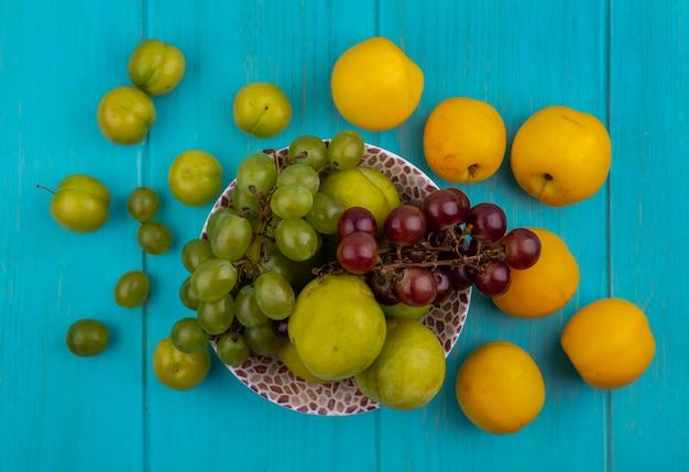 Bovenaanzicht van fruit als druiven groene plukken in kom en patroon van pruimen en nectacots op blauwe achtergrond