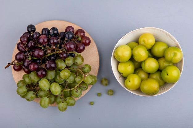 Bovenaanzicht van fruit als druiven op snijplank en kom met pruimen op grijze achtergrond