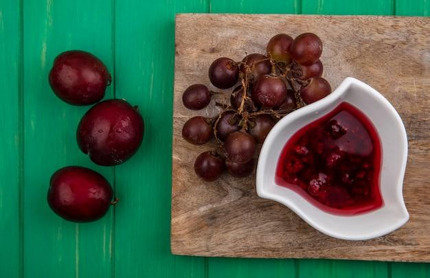 Bovenaanzicht van fruit als druivenmost en pluots met frambozenjam op snijplank op groene achtergrond