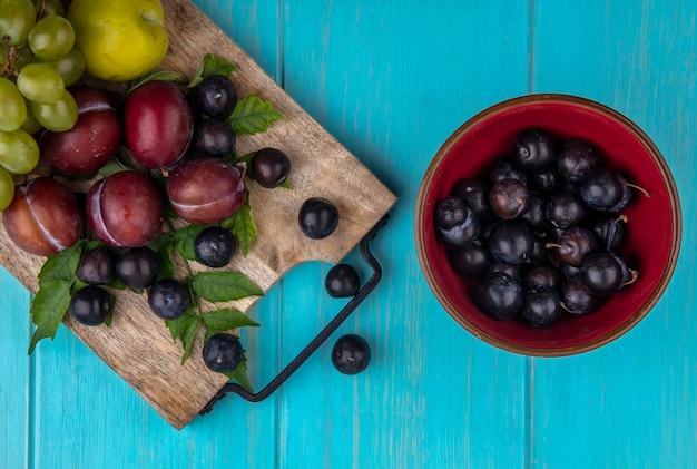 Bovenaanzicht van fruit als druivenplukken met druivenbessen en bladeren op snijplank en kom met druivenbessen op blauwe achtergrond