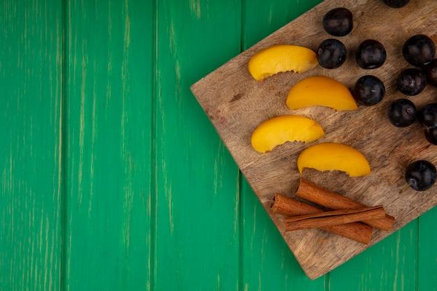 Bovenaanzicht van fruit als gesneden abrikozen en sleedoornbessen met kaneel op snijplank op groene achtergrond met kopie ruimte