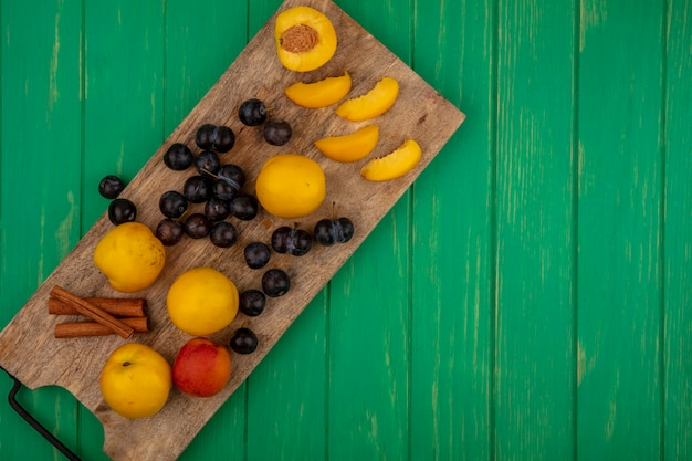 Bovenaanzicht van fruit als gesneden gesneden en hele abrikozen en sleedoorn bessen met kaneel op snijplank op groene achtergrond met kopie ruimte