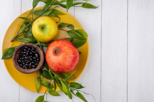 Bovenaanzicht van fruit als granaatappelappel en kom sleedoornbessen met bladeren in plaat op houten oppervlakte met exemplaarruimte