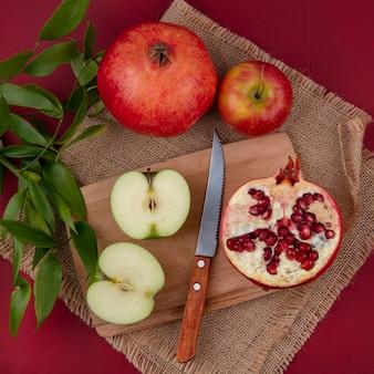 Bovenaanzicht van fruit als half gesneden appel en granaatappel half met mes op snijplank en hele appel en granaatappel met bladeren op zak op rood oppervlak